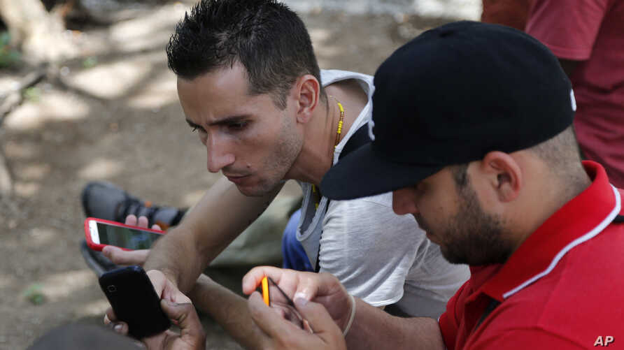 Internet users go online with their smartphones using the first public Wi-Fi hotspot in Havana, Cuba, July 2, 2015.