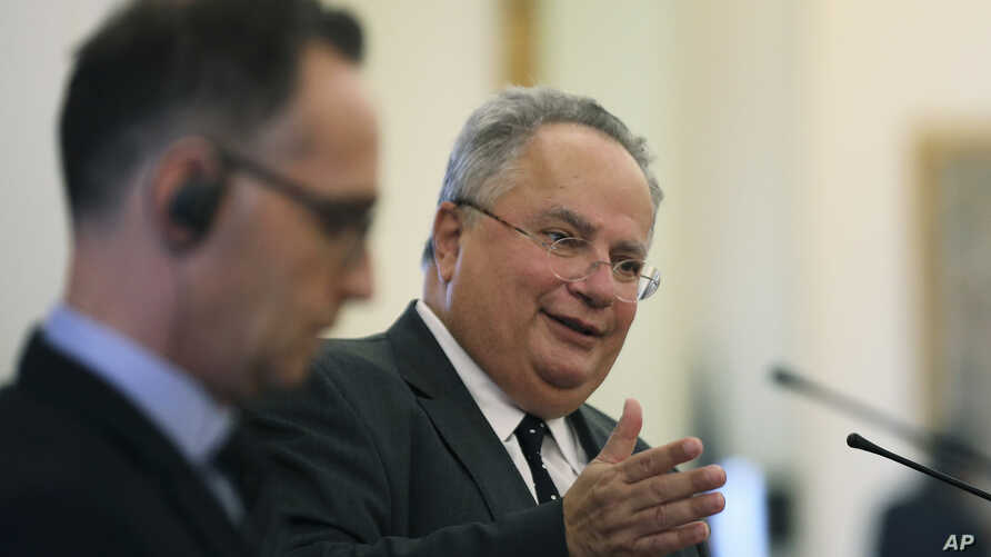 Greek Foreign Minister Nikos Kotzias, right, answers questions next to his German counterpart Heiko Maas during a joint press conference after their meeting in Athens, Greece, Sept. 20, 2018.