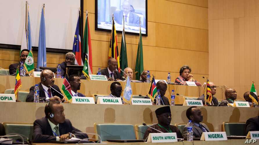 FILE - African Union Chairman Moussa Faki, second left at top, sits with members of the Intergovernmental Authority for Development as they attend a signing ceremony for a cease-fire agreement among South Sudanese parties to end the four-year war in