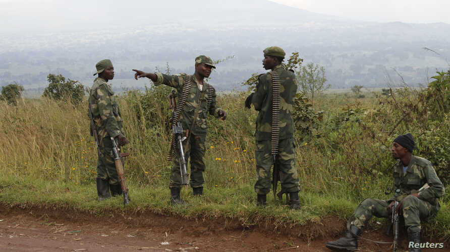 Soldiers from the Democratic Republic of Congo (DRC) rest near the town of Kibumba at its border with Rwanda after fighting broke out in the Eastern Congo town, June 11, 2014.