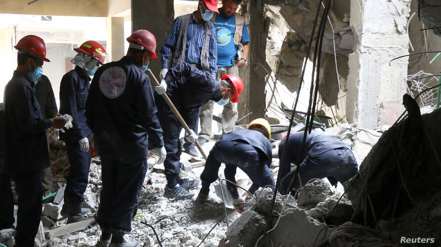 Rescue workers search for bodies still trapped under mounds of debris in Raqqa, Syria, Apr. 9, 2018.