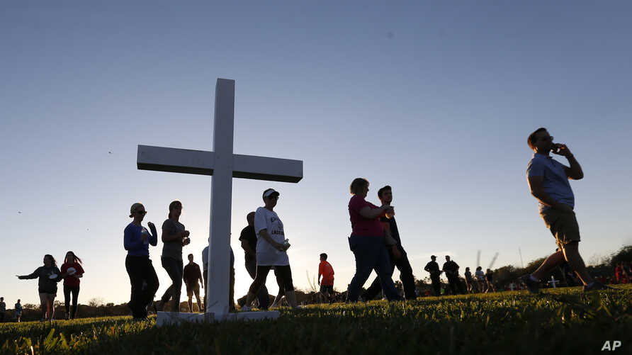 Attendees pass a wooden cross as they arrive at a candlelight vigil for the victims of the shooting at Marjory Stoneman Douglas High School in Parkland, Florida, Feb. 15, 2018.