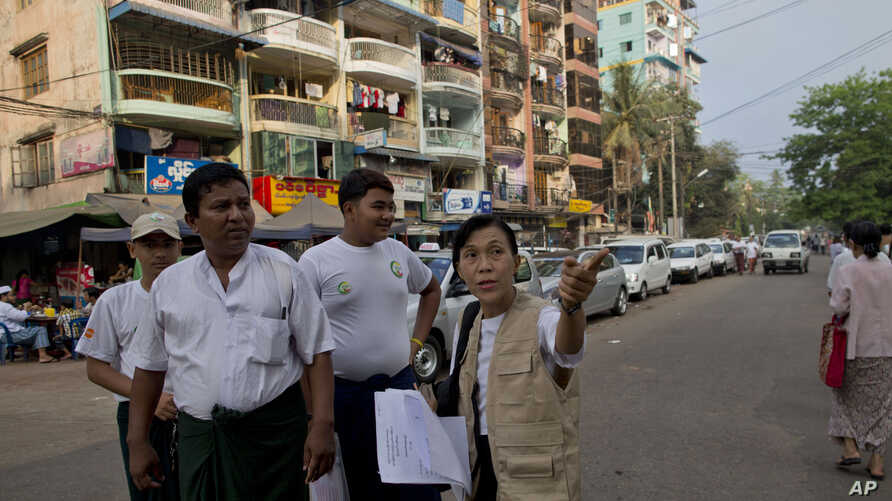 A Burma census enumerator and volunteers walk in a Muslim neighborhood collecting information in Rangoon, March 30, 2014.
