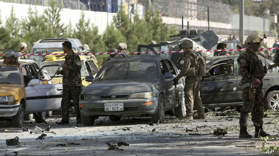 NATO and Afghan security forces inspect the site of a suicide attack in Kabul, Afghanistan, Tuesday, Sept. 16, 2014.  A Taliban suicide car bomber attacked a foreign motorcade just a couple hundred yards (meters) from the U.S. Embassy, unleashing a b...