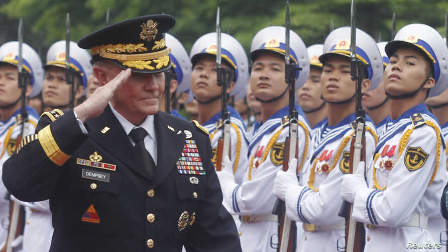 U.S. Chairman of the Joint Chiefs of Staff General Martin Dempsey reviews the honor guard during a welcoming ceremony in Hanoi August 14, 2014.