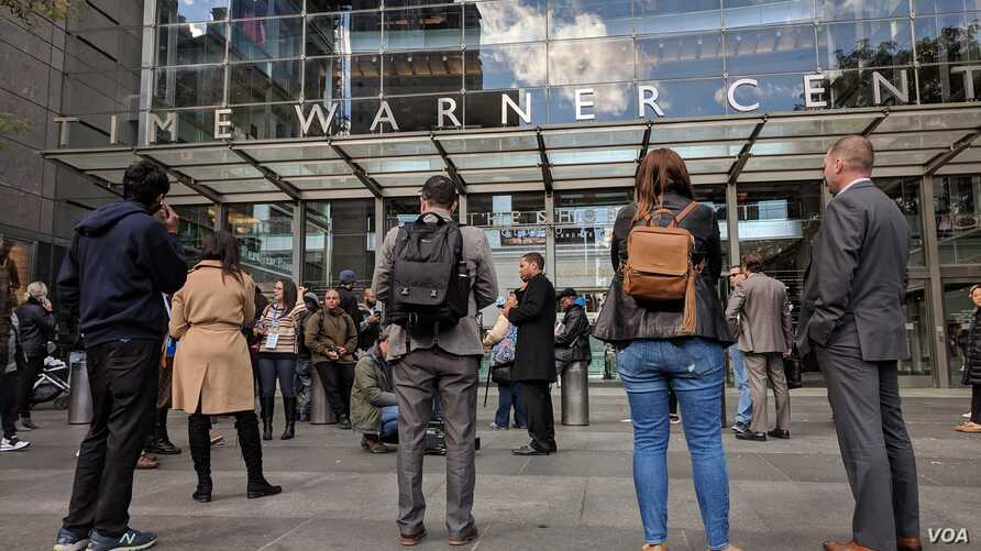 CNN employees stand in front of Time-Warner building where media company headquarters is located in New York, New York, Oct. 24, 2018. (Photo: R. Taylor / VOA)