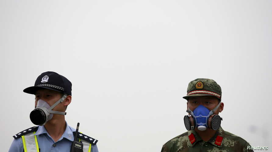 A paramilitary policeman and a policeman, both wearing masks, stand guard at a location within a 3-km (2-mile) exclusion zone from last week's explosion site in Binhai new district in Tianjin, China, Aug. 18, 2015.