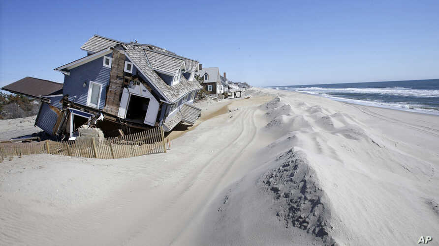 FILE - Homes severely damaged  by Superstorm Sandy are seen along the beach in Mantoloking, N.J., April 25, 2013.   Mantoloking and Ocean City N.J. planned to go to court to seize control of narrow strips of beachfront land from property owners block