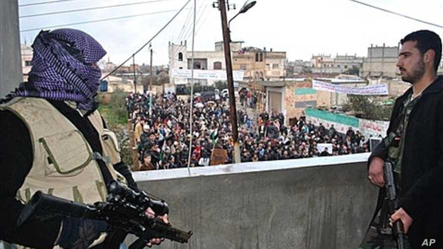 Syrian army defectors secure an anti-Syrian regime protest in the Deir Baghlaba area of Homs province, Jan. 27, 2012.