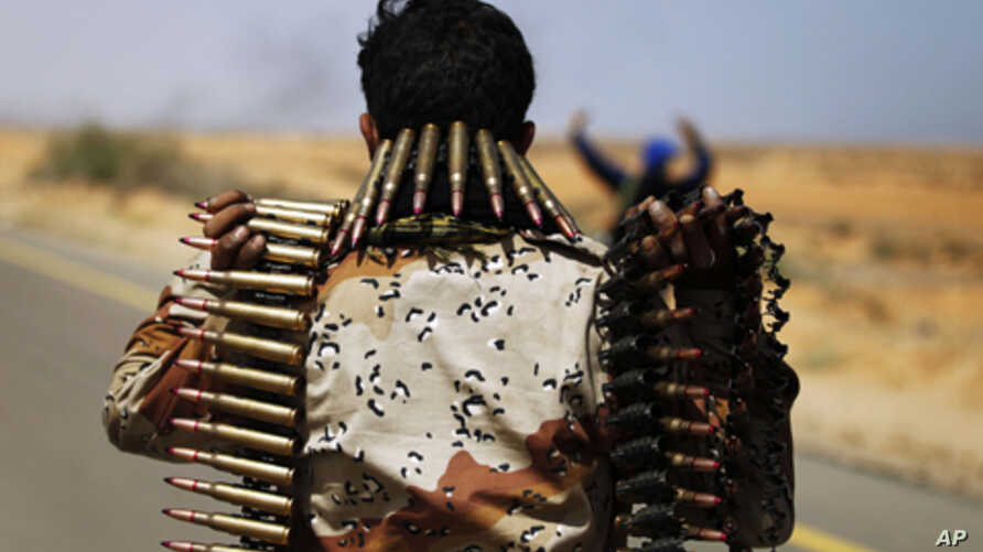 A rebel fighter carries ammunition while advancing in pursuit of forces loyal to Maammar Gadhafi some 120 km (75 miles) east of Sirt in eastern Libya, March 28, 2011