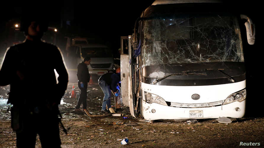 Police officers inspect the scene of a bus blast in Giza, Egypt, Dec. 28, 2018.