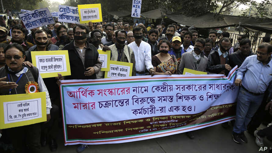 Members of West Bengal Teachers and Allied Educational Employees Federation walk in a procession protesting the demonetization of high-value bills in Kolkata, India, Wednesday, Dec. 28, 2016.