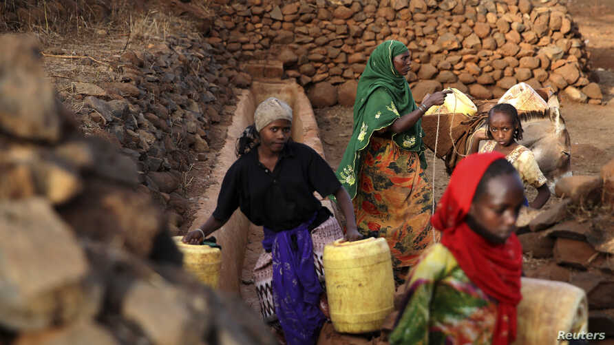 FILE - Women and girls collect water from a well near Marsabit in northern Kenya, Sept. 16, 2014.