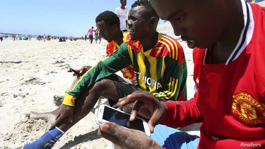 A Somali man browses the internet on his mobile phone at the beach along the Indian Ocean coastline in Somalia's capital Mogadishu, Jan. 10, 2014.