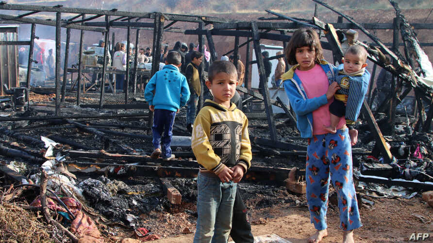 Syrian refugees check the damage following a fire that ripped through their refugee camp in the village of Yammouneh in Lebanon's eastern Bekaa Valley on Dec. 3, 2018.
