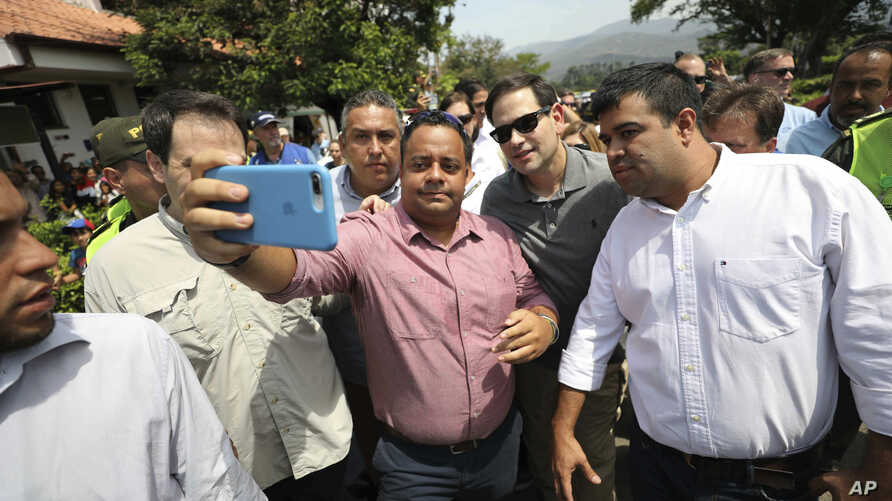 U.S. Senator Marco Rubio, R-Fla., in sunglasses, poses for photos with people near the Simon Bolivar International Bridge, which connects Colombia with Venezuela, in La Parada, near Cucuta, Colombia, Sunday, Feb. 17, 2019.