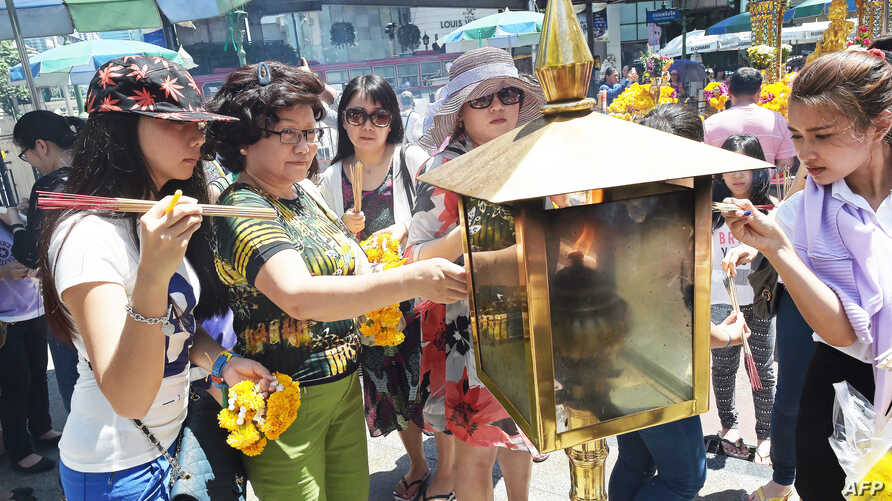 Women light incense sticks before offering prayers at the reopened Erawan shrine - the popular tourist site where 20 people were killed on August 17 in a bomb blast - in central Bangkok on Aug. 20, 2015.