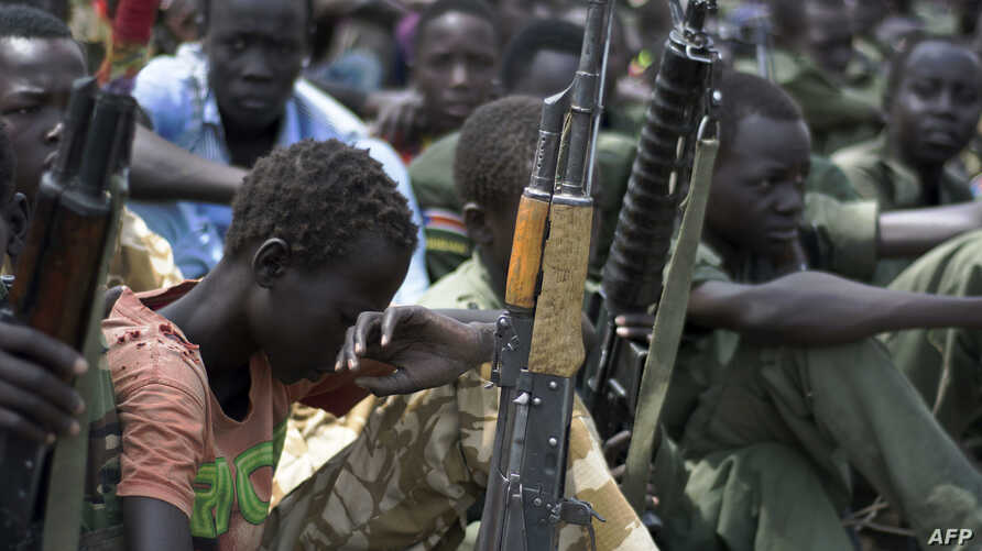 Boys with their rifles sit at a ceremony of the child soldiers disarmament, demobilization and reintegration in Pibor, Jonglei State, South Sudan, oversawn by UNICEF and partners, Feb. 10, 2015.