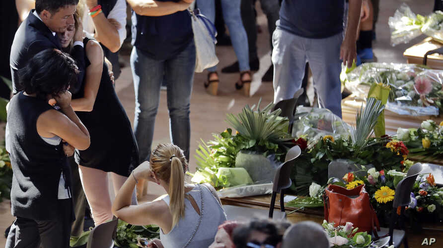 Italian Premier Matteo Renzi, left, comforts a woman at the end of the state funeral service for some of the victims of the earthquake that hit central Italy last Wednesday, in Ascoli Piceno, Italy, Aug. 27, 2016