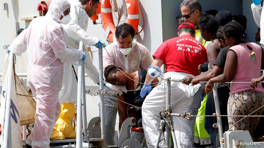 A woman is helped by medical staff abroad the Italian Navy vessel Vega at the Reggio Calabria harbor, southern Italy, May 29, 2016.
