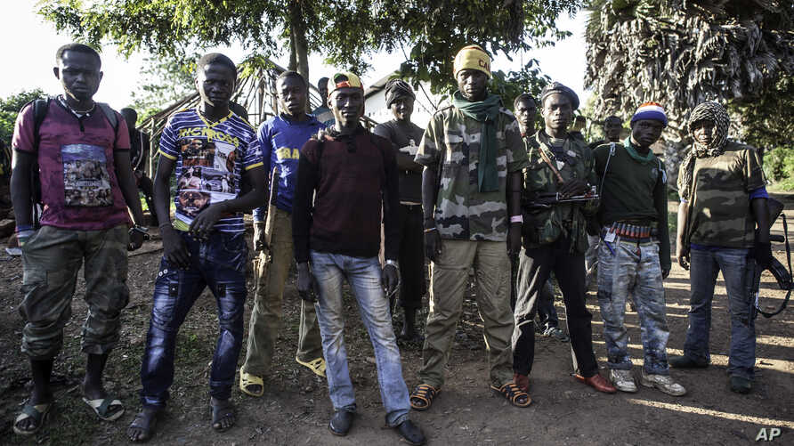FILE - Anti-balaka fighters stand for a photo in Boda, Central African Republic, Aug. 28, 2014.
