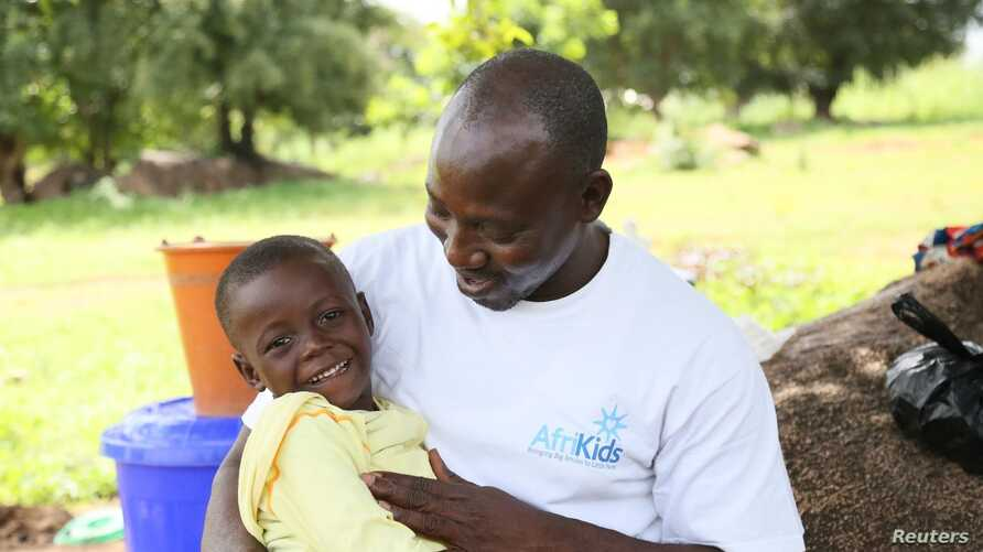 FILE - Joseph Asakibeem, project manager with charity AfriKids and winner of the Bond Humanitarian Award 2018 for his work with disabled children, hugs a child, Richmond, in Ghana's Upper East Region, Sept. 2014..