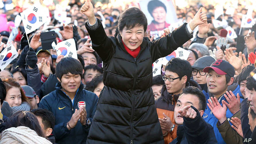 South Korea's presidential candidate Park Geun-hye of ruling Saenuri Party raises her arms  during her presidential election campaign in Busan, South Korea, Dec. 18, 2012.