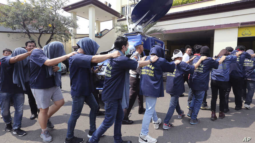 FILE - Police officers escort men arrested in a raid on a gay sauna at North Jakarta police headquarters in Jakarta, Indonesia, May 22, 2017. Indonesian police detained dozens of men in a weekend raid on a gay sauna in the capital, another sign of gr...