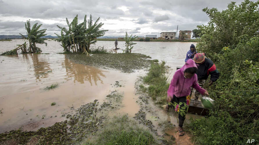 Workers take a makeshift boat to cross flooded vegetable gardens in Madagascar's capital Antananarivo, March 9, 2017.