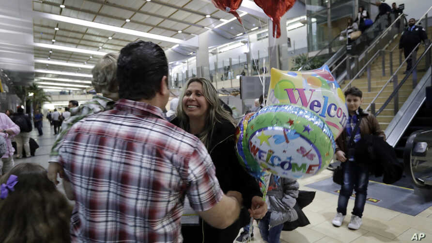 FILE - Nadia Hanan Madalo, center, hugs her brother Gassan Kakooz at the airport after arriving from Iraq, March 15, 2017, in San Diego. Madalo and her family, refugees forced to flee after the Islamic State invaded several years ago, arrived in San