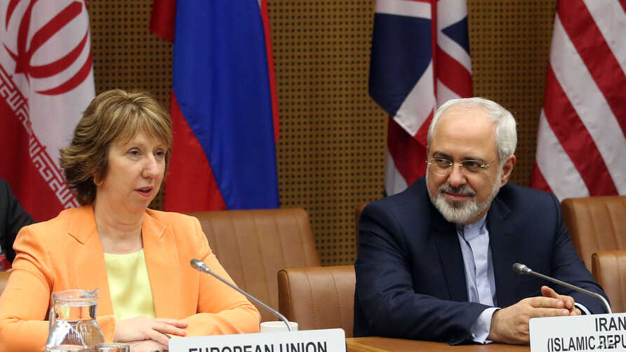 European foreign policy chief Catherine Ashton, left, and Iranian Foreign Minister Mohamad Javad Zarif, right, wait for the start of closed-door nuclear talks in Vienna, Austria, Mar. 19, 2014.