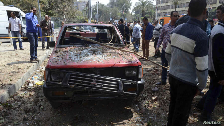 People stand near a damaged car after explosions near Cairo University, April 2, 2014.