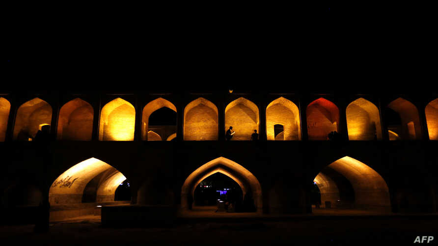 "Iranians walk next to the ""Si-o-Se Pol"" bridge (33 Arches bridge), April 12, 2018, over the Zayandeh Rud river in Isfahan, which now runs dry because of water extraction before it reaches the city. The 295-meter-long bridge was completed in 1596 by I"
