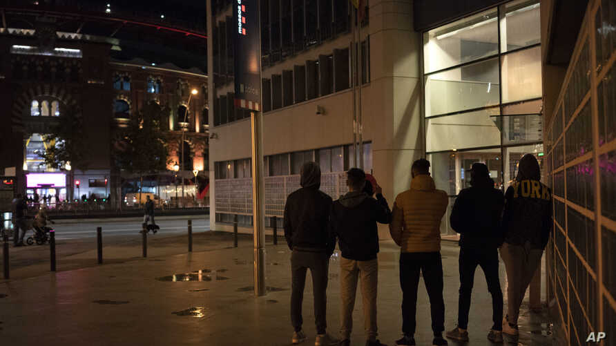 In this Nov. 9, 2018 photo, unaccompanied minors from Morocco seeking shelter, stand outside a police station in Barcelona, Spain.