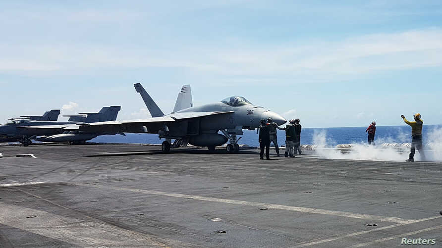 An F18 fighter prepares to take off at the flight deck of the USS Theodore Roosevelt while transiting the South China Sea, April 10, 2018.
