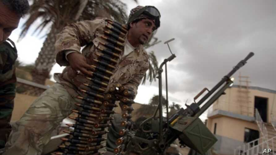 A Libyan army paratrooper who defected and joined the popular uprising against leader Moammar Gadhafi loads an anti-aircraft machine gun atop a truck in the eastern Libyan port city of Benghazi, February 26, 2011