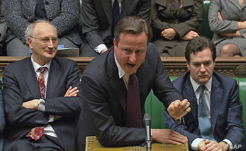 Britain's Prime Minister David Cameron (C) is flanked by Chancellor of the Exchequer George Osborne (R) and Leader of the House of Commons George Young during a parliamentary debate on last week's European Union summit, in London, December 12, 2011.
