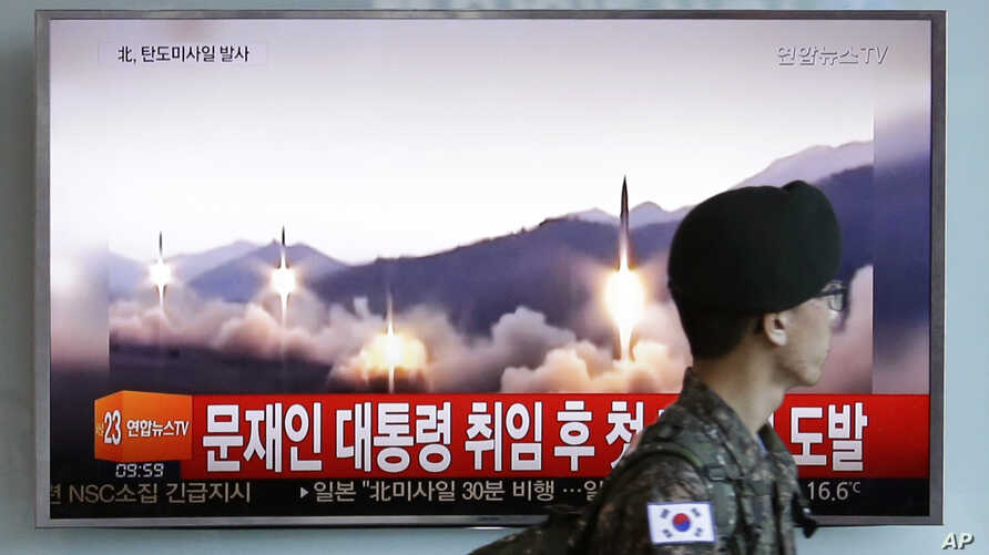 A South Korean army soldier walks by a TV news program showing a file image of missiles being test-launched by North Korea, at the Seoul Railway Station in Seoul, South Korea, May 14, 2017.