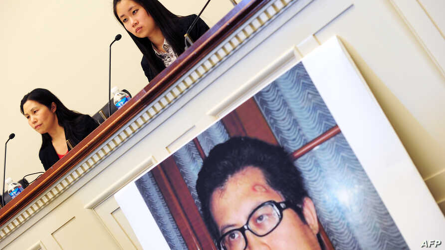 FILE - Zhang Qing, left, wife of Chinese human rights activist Guo Feixiong, and daughter Yang Tianjiao speak at a press conference before a hearing of a House Foreign Affairs Committee subcommittee in Washington, D.C., October 29, 2013.