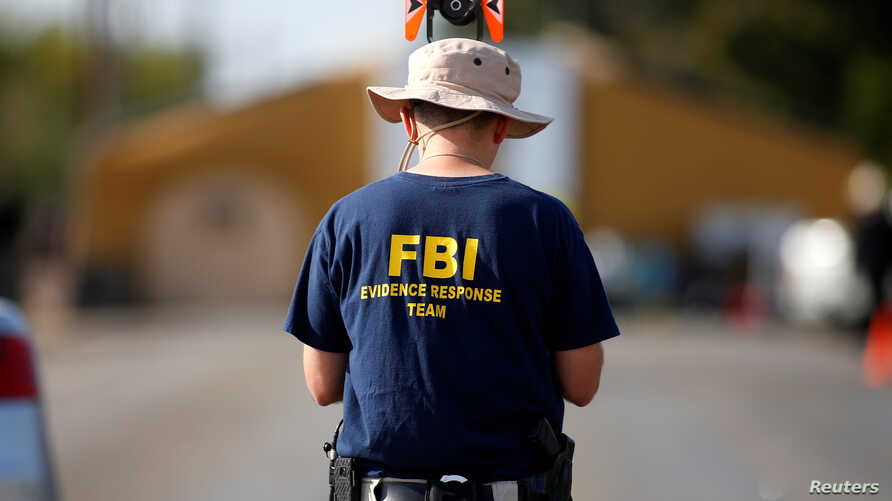 FILE - An FBI agent investigates the site of the shooting at the First Baptist Church of Sutherland Springs, Texas, Nov. 7, 2017.