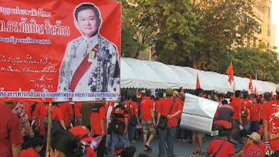 One red-shirted protester in Thailand holds a picture of former Prime Minister Thaksin Shinawatra, who was ousted in a coup in 2006