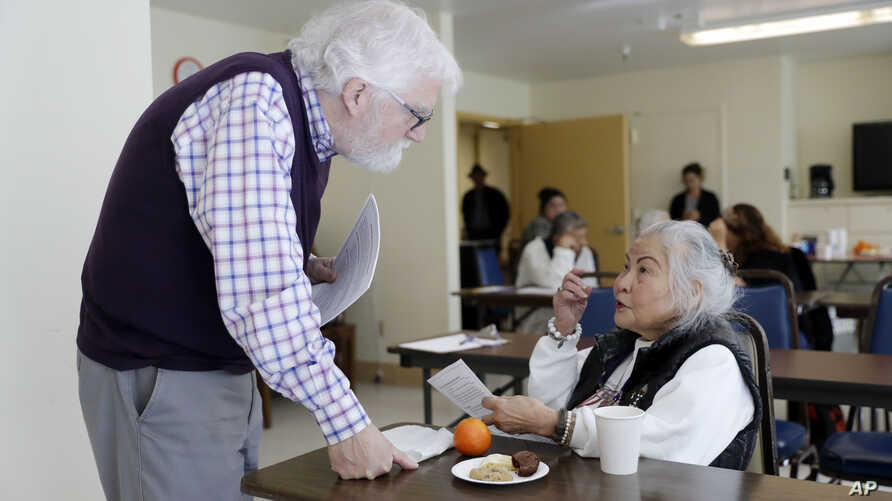 In this April 13, 2018 photo, Patrick Arbore, left, talks to Corazon Leano as he conducts an anti-bullying class at the On Lok 30th Street Senior Center in San Francisco.