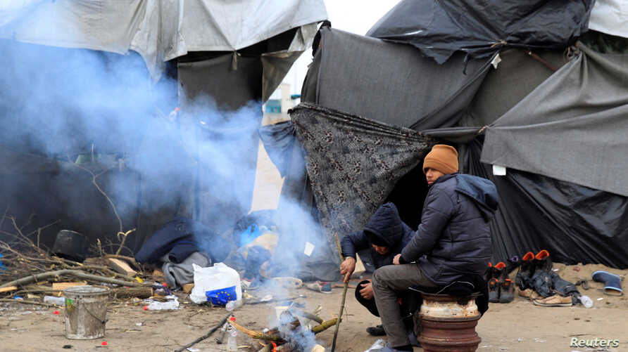 Migrants warm themselves by the fire at a makeshift camp in the transit zone on the Serbian-Hungarian border near Horgos, Serbia, Jan. 9, 2017.