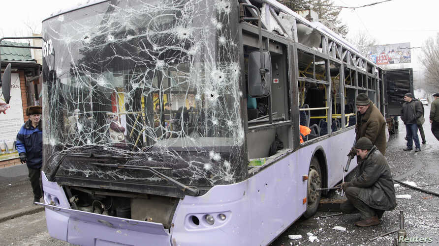 People surround a damaged trolley bus that was shelled, killing at least 13 people, in Donetsk, Ukraine, Jan. 22, 2015.