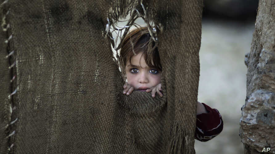 A Pakistani child, who was displaced with her family from Pakistan's tribal areas, looks out through a hole of a makeshift curtain at the entrance of her family's home, in a poor neighborhood on the outskirts of Islamabad, Pakistan, Monday, Jan. 28,