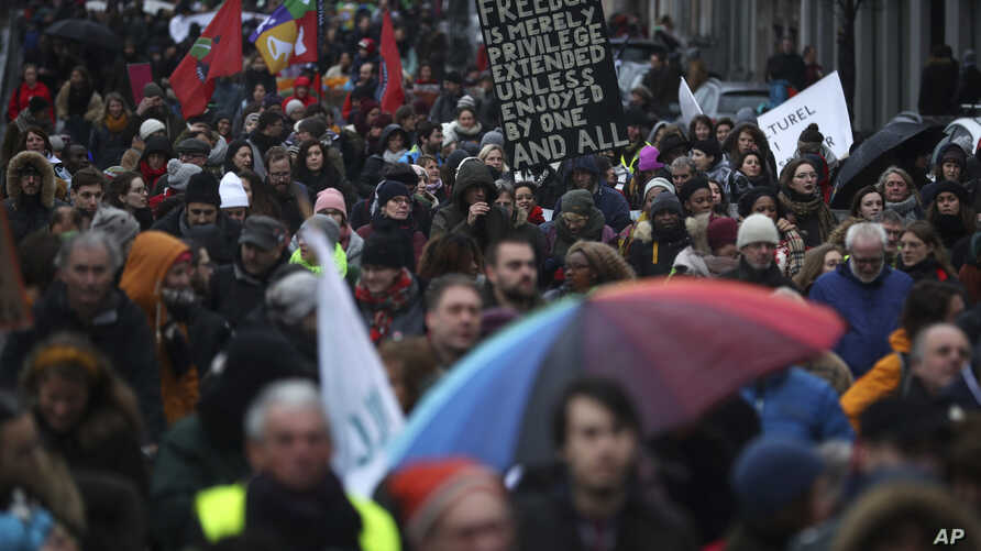 People march under rain during a demonstration in support of migrant people seeking to enter Europe, in Brussels, Saturday, Jan. 12, 2019.