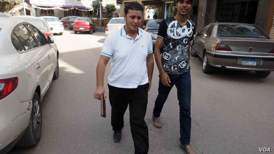 Once physically female, Mohammad Alaam (L) and his friend stroll through a Cairo suburb, June 13, 2016. (H. Elrasam/VOA)