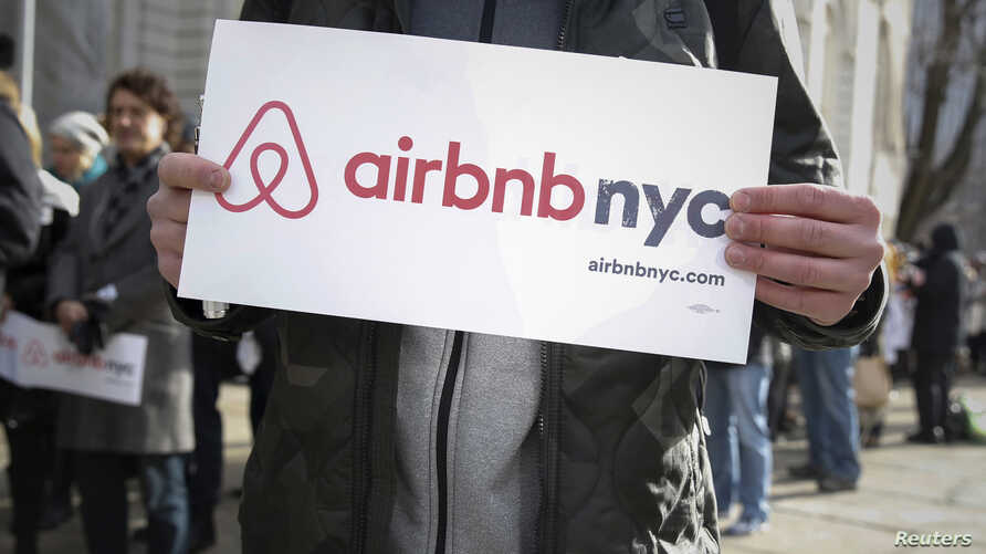 """Supporters of Airbnb stand during a rally before a hearing called """"Short Term Rentals: Stimulating the Economy or Destabilizing Neighborhoods?"""" at City Hall in New York, Jan. 20, 2015."""