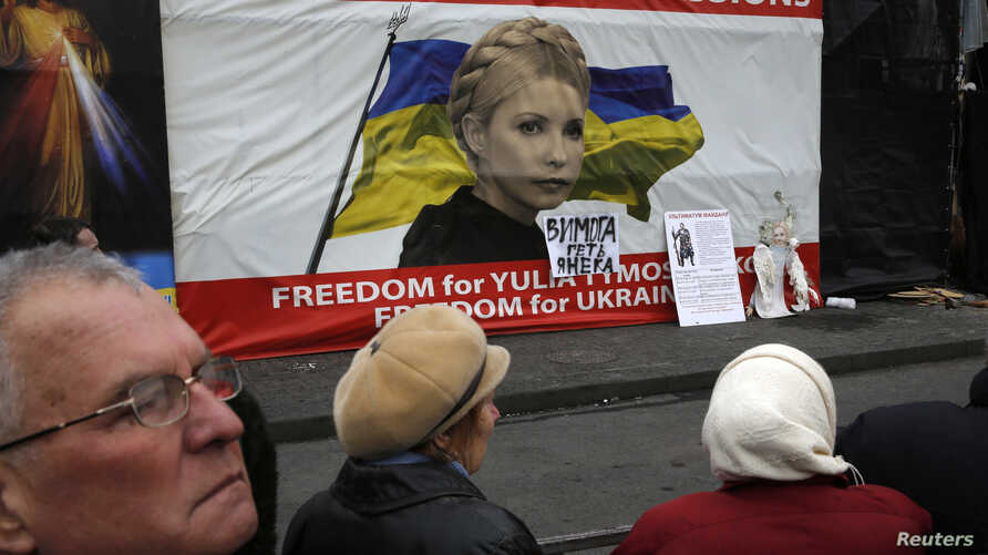 People discuss in front of a poster showing jailed Ukrainian opposition leader Yulia Tymoshenko in central Kyiv, Feb. 22, 2014.