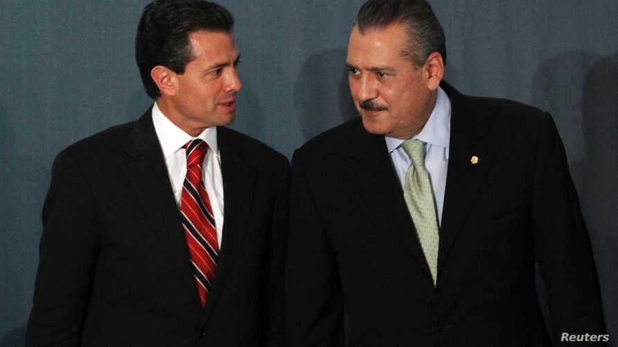 FILE - Mexico's (then) President-elect Enrique Pena Nieto (L) and congressman Manlio Fabio Beltrones attend a meeting with newly elected senators and lawmakers of the Institutional Revoluntionary Party (PRI) in Mexico City, Aug. 9, 2012.